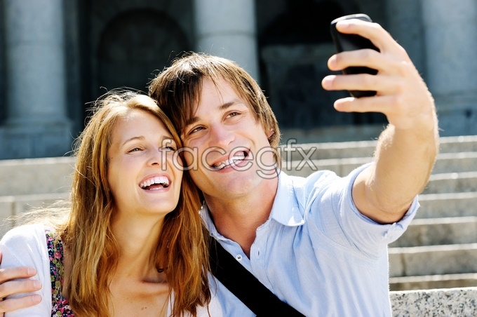 Couple taking pictures with their cell phones in Europe and America HD picture